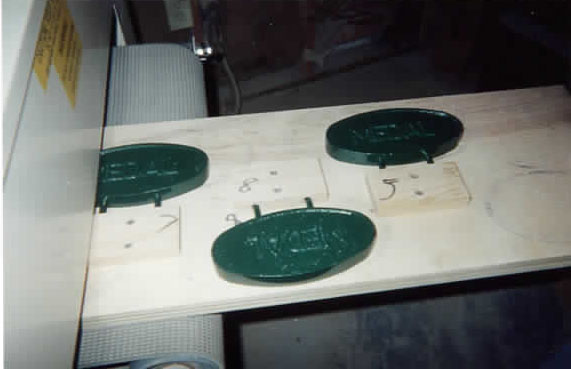 PAINTED PLAQUES GO IN — Art mounts his painted castings on a jig and runs them through his Woodmaster Drum Sander.