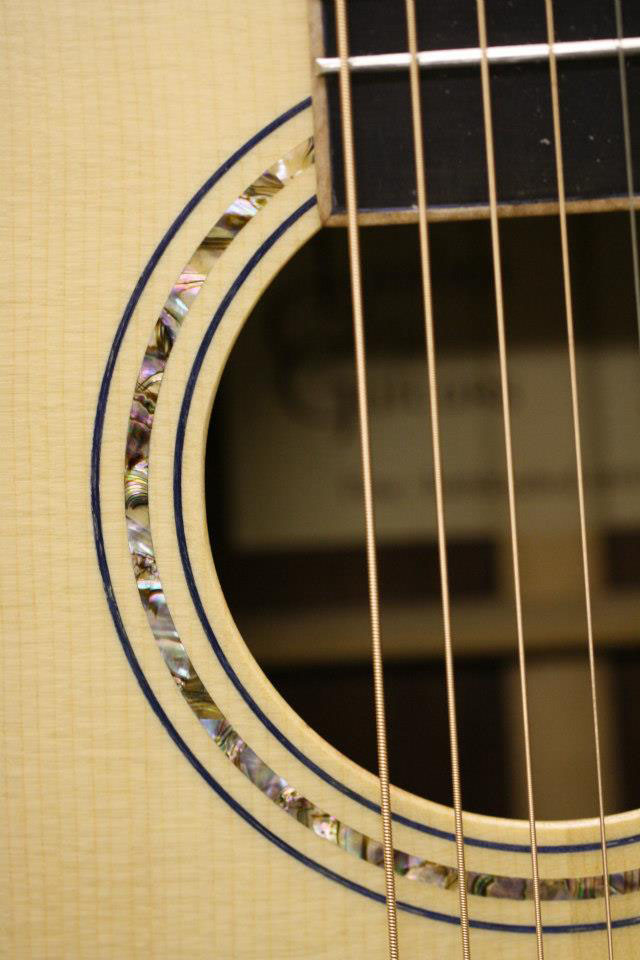 """This guitar has a Sitka spruce top,"" John tells us. ""I trimmed the sound hold with Abalone shell."""