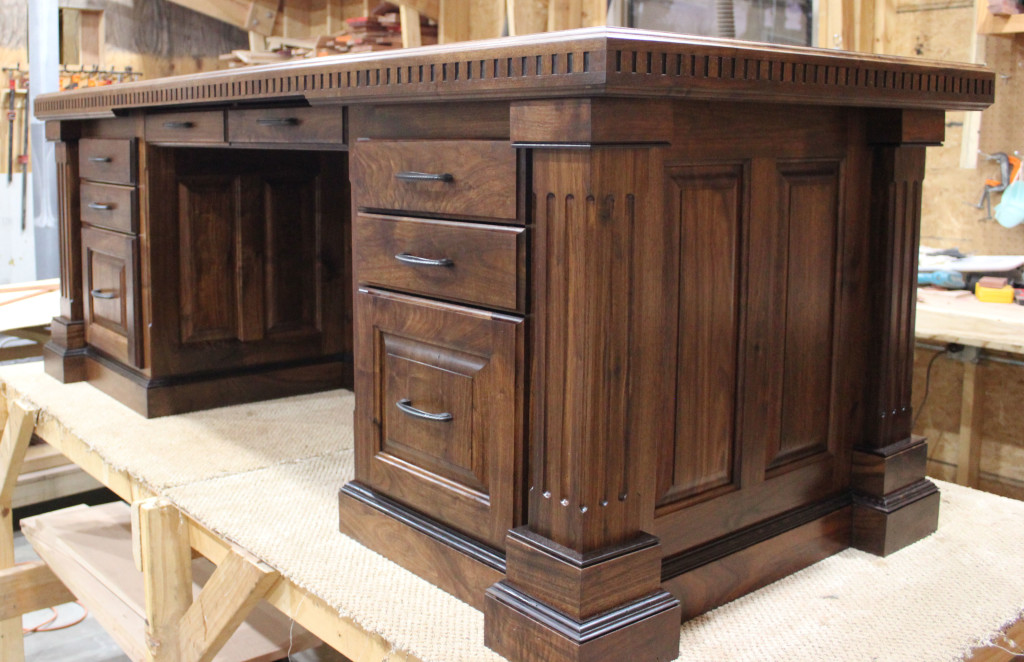 "This outstanding executive desk is a full 36"" x 72"". It's made of Black Walnut and features raised panel construction, Wenge trim detailing, and more including columns with ""Coves & Flutes"" and top with ""Dental Edge Banding."""