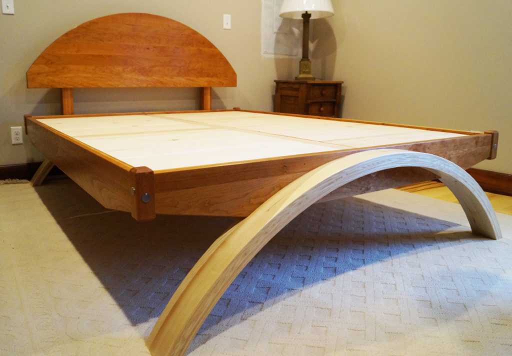 "For this queen-size platform bed, I matched the arc of the cherry headboard with the laminated ash arched legs. These two woods contrast each other nicely. (The Cherry was re-purposed 3/4"" thick molding, ripped to 5/8"" thick, sanded both sides on my Woodmaster, and surface-glued to make 5/4 thick boards.) The Oak center beam supports the head and footboard making a very stable connection. The pine boards create a solid ""platform""."