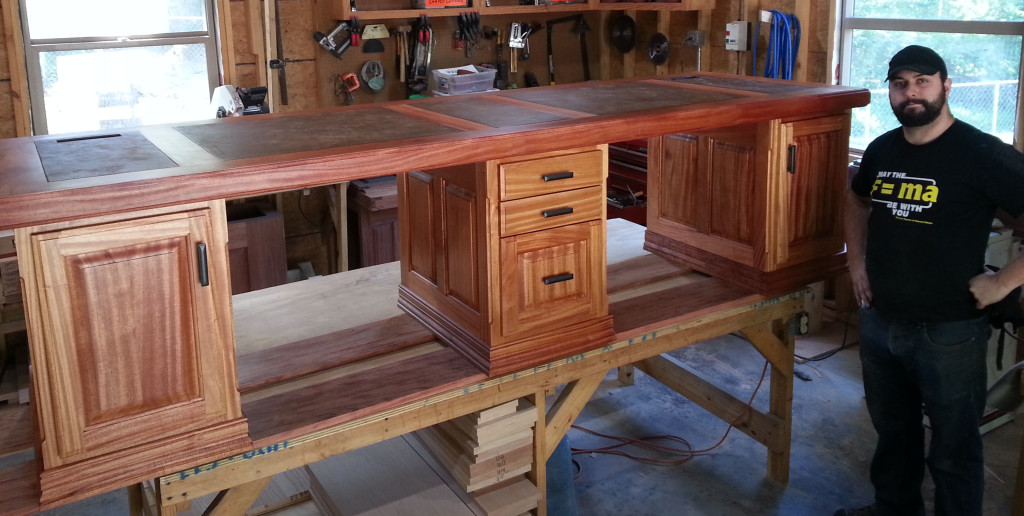 Ray's son Anthony shows off the company's unique two-person desk; their original design made of mahogany.