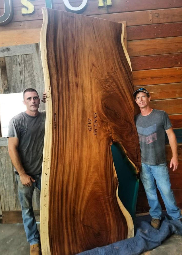 Josh (right) and employee, Barry Brooks, give a sense of the scale of one of their big, big slabs, sustainably harvested in Central America.